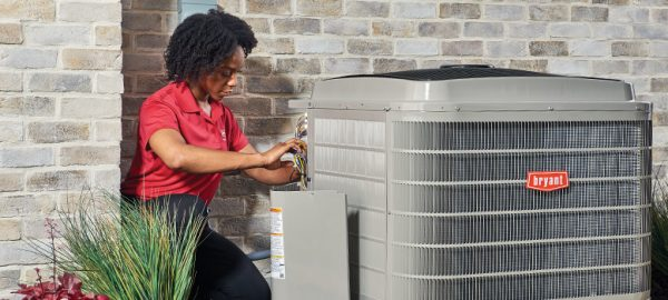 HVAC technician repairing an air conditioner