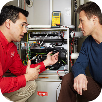 HVAC technician discussing furnace maintenance with homeowner