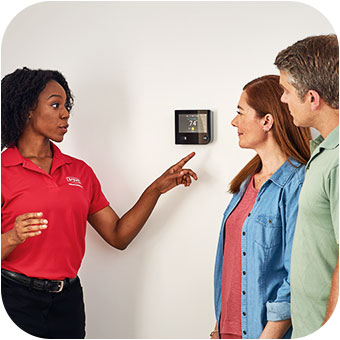 HVAC technician discussing the thermostat with homeowners after a boiler repair