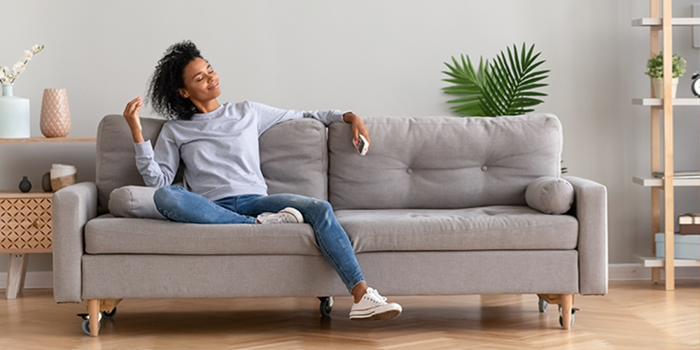 Woman enjoys her ductless system while relaxing