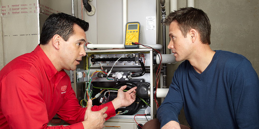 Expert tech shows homeowner furnace maintenance tips in the basement.