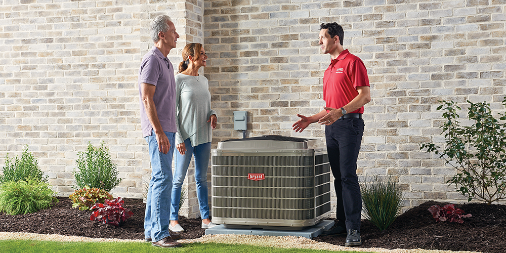 Technician in red shirt explains to couple how they can save money on air conditioning.